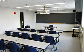This photo shows the room the lectures were given in with rows of tables and moveable chairs for a maximum of 20 students.  There is an overhead and manual slide projector, a large chalkboard at the front and a window to the students right.