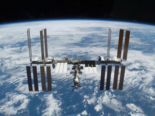 Photograph of the International Space Station with the blue oceans of Earth visible below.