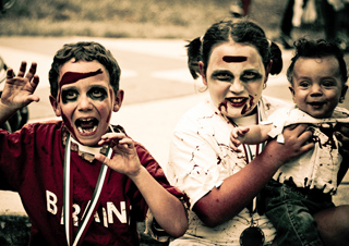 Three kids dressed in zombie costumes posing for the camera.