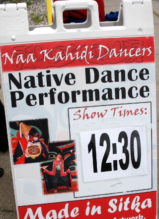 Sidewalk sandwich board advertises the next dance performance at 12:30 by the Naa Kahidi Dancers, located in Sitka, Alaska.