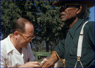 A white doctor gives a shot in the arm of an elderly black man.