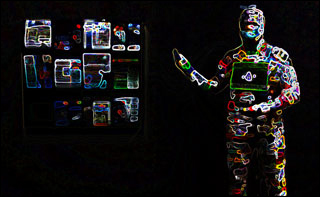 A human form stands in darkness, wearing a bodysuit illuminated from head to toe with various multi-colored circuits.