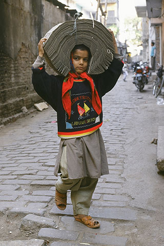 A young boy in India walks while carrying a tied up bundle of punched-data cards on his head.