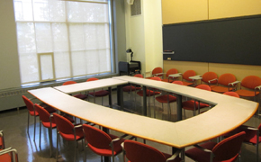 Classroom with 14 red chairs arranged around tables in a rectangular position. A blackboard runs along wall. Floor to ceiling windows.