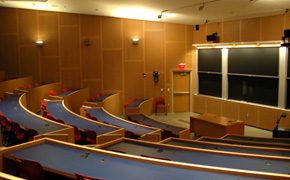 A large classroom with tiered seating and several chalkboards.