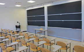 A medium-sized classroom with student desks and several chalkboards.