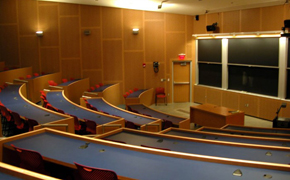 A large classroom for 100 students with tiered seating and several blackboards.