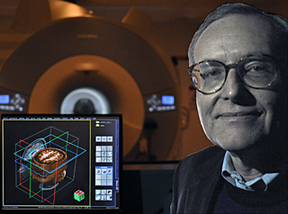 Photo of Professor Gabrieli sitting next to a computer display of human brain images, with fMRI scanner in the background.