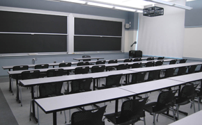 A classroom with four long tables spanning the classroom, chairs behind each table, and four sliding chalkboards at the front.