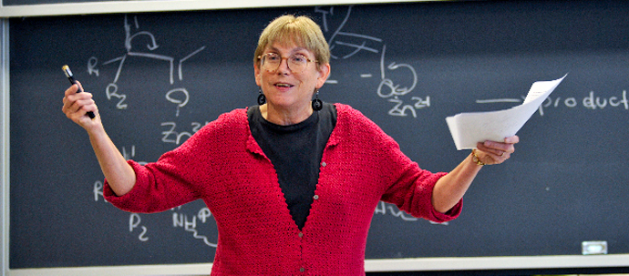 A teacher in a red sweater standing in front of a blackboard, gesturing to her audience.