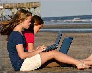 Two girls working on the beach.