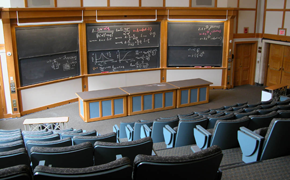 This classroom, which seats 135, has stadium-style rows of seats. At the front, there is a large table and six sliding chalkboards in a 3 wide by 2 high configuration.