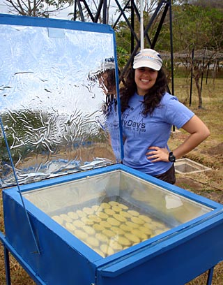 Photo of a student standing outdoors next to a box containing cookies, with clear plexiglass top and a large foil solar reflector.