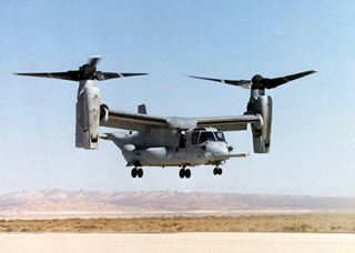 A photo of an CV-22 Osprey in rotorcraft mode, hovering above the ground.