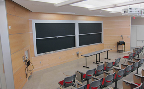 Tiered lecture hall with tablet arm desks, and chalkboards and projector at the front of the room.