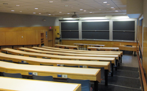 Classroom with even rows of long tables, each with about nine chairs. Six chalkboards at the front; projector mounted on the ceiling.