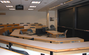 A large, modern classroom with faceted tiered seating, blackboards, and a projector.