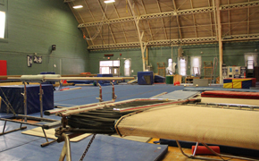 Gymnastics gymnasium featuring a trampoline and parallel bars in the foreground, a large blue practice mat in the middle of the space, and various incline mats and equipment in the background.