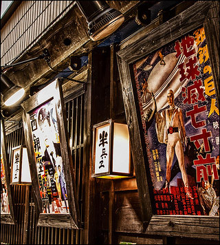 A photo of older movie posters outside of a wooden building.
