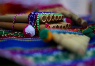 Photograph of a pan flute on a colorful blanket.