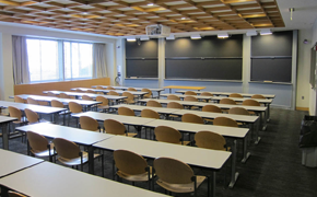 A lecture-style classroom with desks and chalkboards.