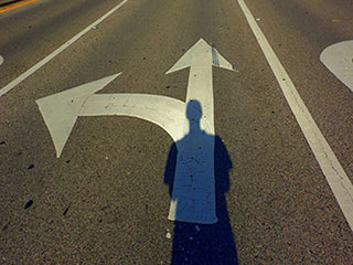 A man's shadow falls on two arrows painted on a road—one arrow points left and the other points straight ahead.
