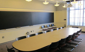 Photo shows the classroom with a long, oval seminar table surrounded by chairs and chalkboards on the walls.