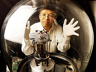 A man wearing white latex gloves posing both hands on a glass chamber containing a mechanical device.