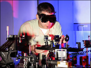 Researcher working with an optics table in laboratory.