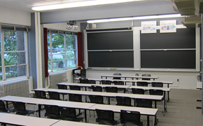 This classroom photo shows five rows of student tables, each with six chairs. At the front there is a smaller table and two chairs, and two sets of sliding chalkboards.