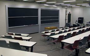 Classroom with rectangular tables and chairs arranged in tiered rows. A small brown table is positioned at the front of the room. It sits in front of two chalkboards.