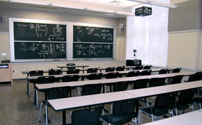 Photo of a classroom with long tables arranged with chairs so that they face the four chalkboard panels in the front of the room.