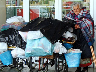 An elderly woman on crutches waits outside a train station with  bags, buckets, and blankets resting on two wheelchairs beside her.