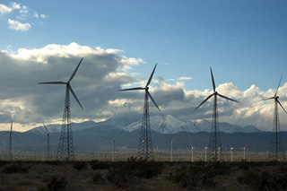 Windmills in a wind farm, mountains in the background.