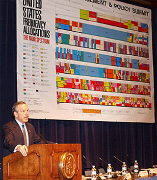 Commerce Secretary Evans presenting in front of a chart of the electromagnetic spectrum.