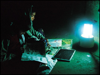 A girl reading in the dark with a lantern.