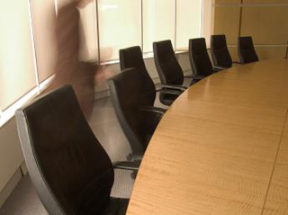 A photo of a person dashing across a typical boardroom.