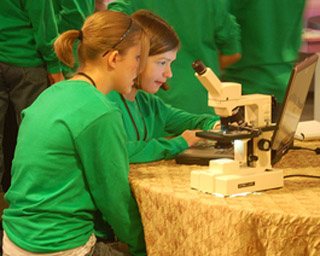 Two girls in green shirts use a laptop computer and microscope.