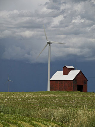 A wind turbine towers over a small red farmhouse.