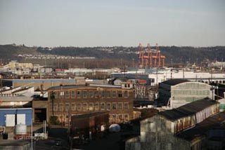 A distant photo of big buildings, warehouses, and cranes.