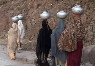 Pakistani women clad in traditional clothing carrying water in metalic vessels on their heads .
