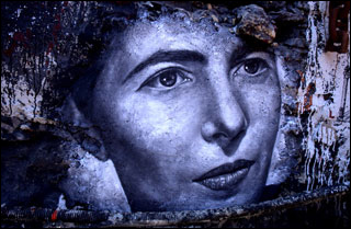 A black and white mural of a woman's face, with  large eyes, a pointed nose, and thin lips, closed in a serious expression.