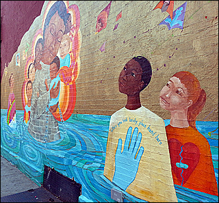 A photographA mural painted on a wall features a body of water in which an African-American boy and a Caucasian girl stand.  The image of a woman surrounded by children is next to them. of a pregnant woman, in a blue shirt, holds her belly.