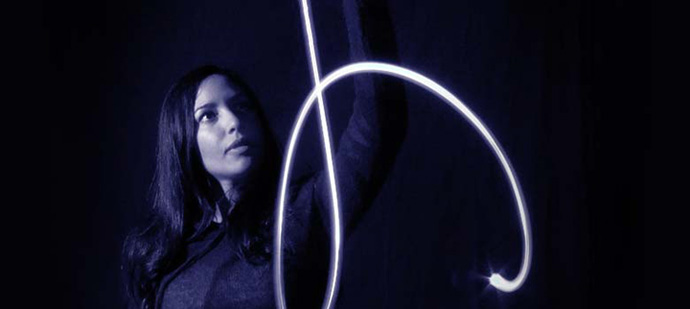 A photo of a woman and a beam of blue light in the dark.