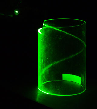 A photograph of green laser light hitting the edge of a transparent cylinder and then curling into a helix due to total internal reflection.